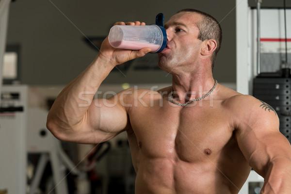 Muscular Man Drinking Water From Shaker Stock photo © Jasminko