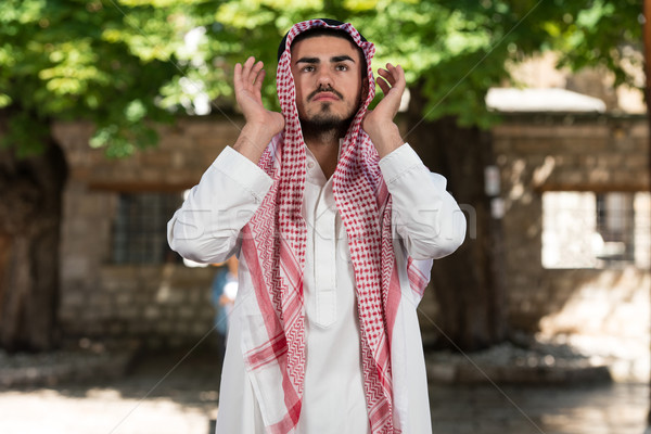 Young Muslim Man Making Traditional Prayer To God While Wearing A Traditional Cap Dishdasha Stock photo © Jasminko