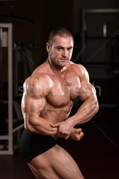 Young Bodybuilder Flexing Muscles Stock photo © Jasminko