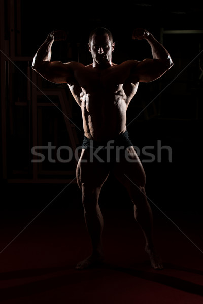 Bodybuilder Standing In The Gym And Flexing Muscles Stock photo © Jasminko