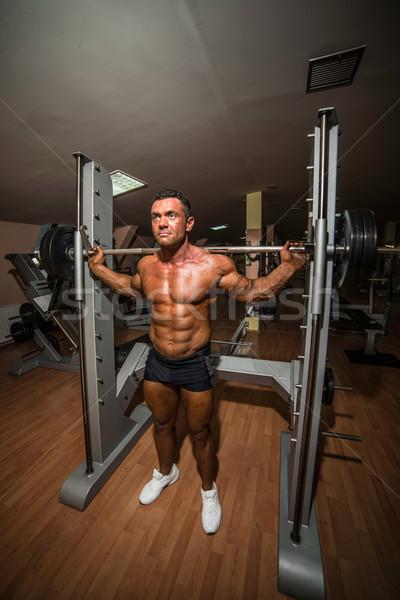bodybuilder doing squat with barbell Stock photo © Jasminko