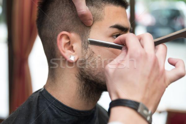 Hairdresser Shaving Man's Chin With A Straight Razor Stock photo © Jasminko