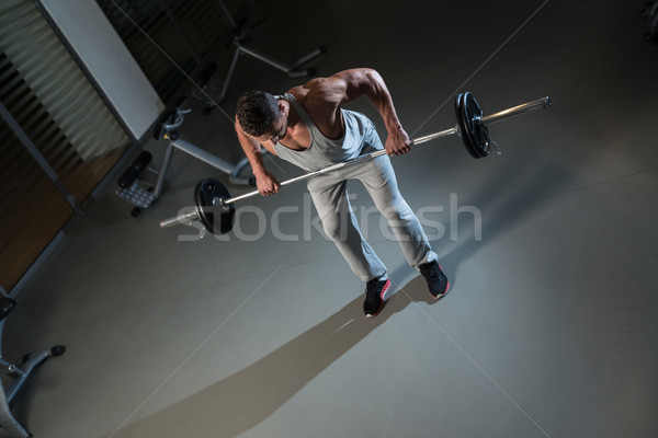 Man Doing Exercise For Back With Barbell Stock photo © Jasminko