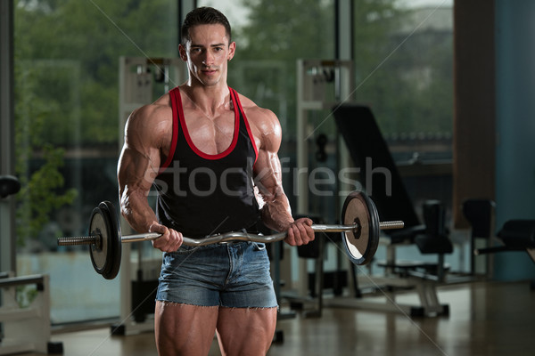 Man In The Gym Exercising Biceps With Barbell Stock photo © Jasminko