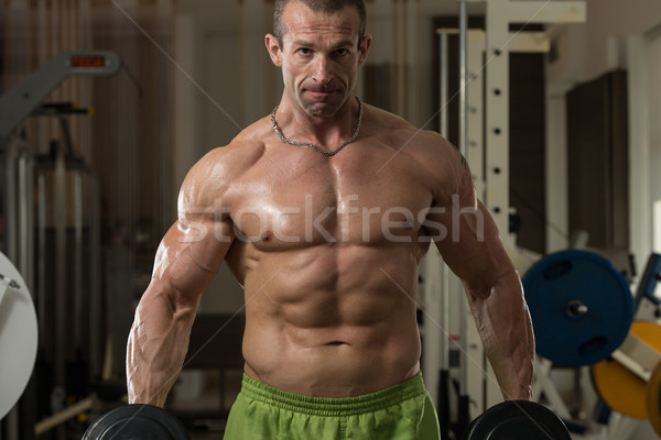 Bodybuilder Exercising Biceps With Dumbbells Stock photo © Jasminko
