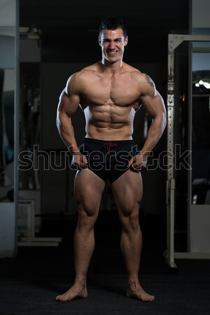 Serious Men Standing And Flexing Muscles Stock photo © Jasminko