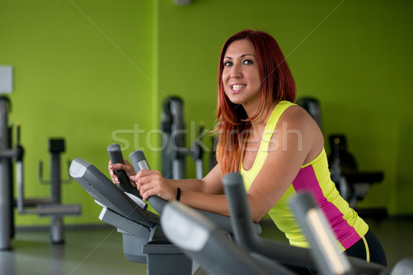 Happy woman working out on a gym cycle Stock photo © Jasminko