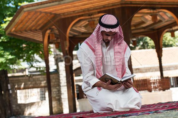 Muslim Man In Dishdasha Is Reading The Quran Stock photo © Jasminko