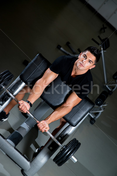 Handsome muscular man exercising in Gym Stock photo © Jasminko