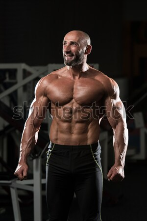Muscular Men Flexing Muscles On Black Background Stock photo © Jasminko