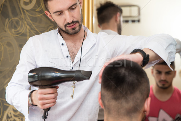 Stylist Drying Hair Of A Male Client Stock photo © Jasminko
