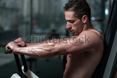 Muscular Man Exercising Biceps In Gym Stock photo © Jasminko