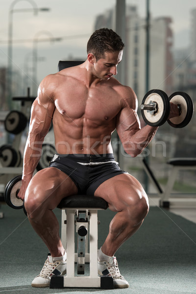 Bodybuilder Exercising Biceps With Dumbbells Stock photo © Jasminko
