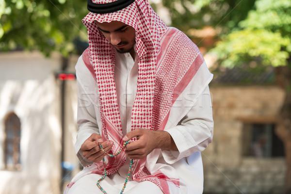 Közelkép férfi kezek imádkozik rózsafüzér fiatal Stock fotó © Jasminko