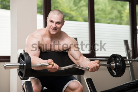Men In The Gym Exercising Biceps With Barbell Stock photo © Jasminko