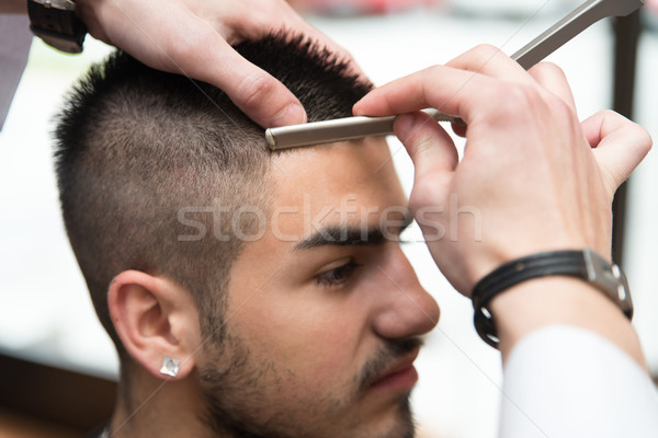 Hairdresser Shaving Man's Forehead With A Straight Razor Stock photo © Jasminko