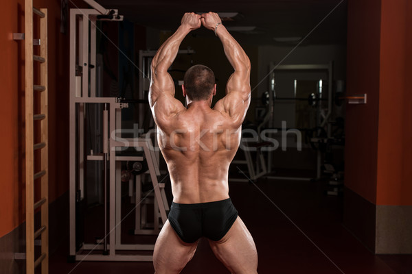 Bodybuilder Performing Rear Double Biceps Pose Stock photo © Jasminko