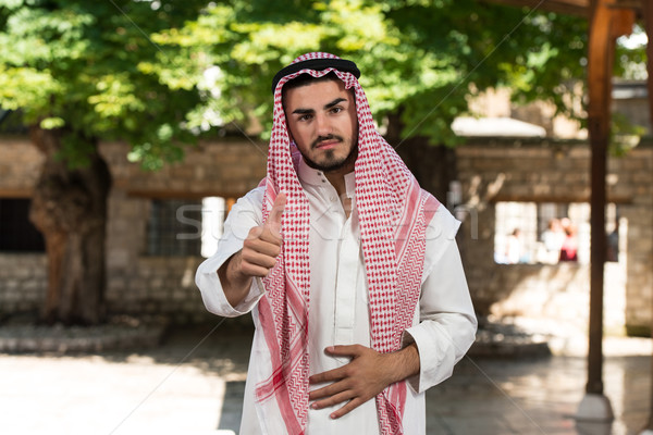 Handsome Middle Eastern Holding Thumbs Up Stock photo © Jasminko