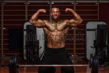 male bodybuilder doing shoulder press whit dumbbell Stock photo © Jasminko
