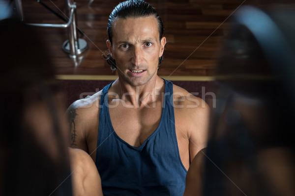 Man in gym on machine exercising Stock photo © Jasminko