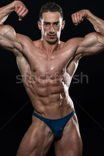 Young Bodybuilder Flexing Muscles Isolate On Black Blackground Stock photo © Jasminko