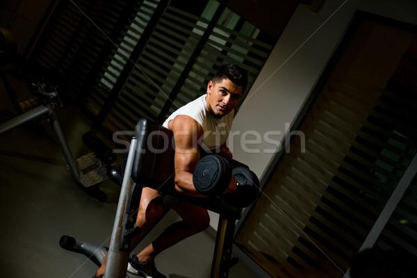 Man lifting dumbell in gym Stock photo © Jasminko