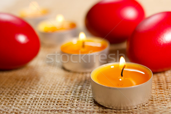 Closeup of rounded candles placed between three red egg Stock photo © jaycriss
