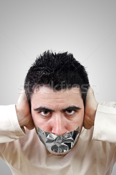Angry young man having gray duct tape on his mouth Stock photo © jaycriss