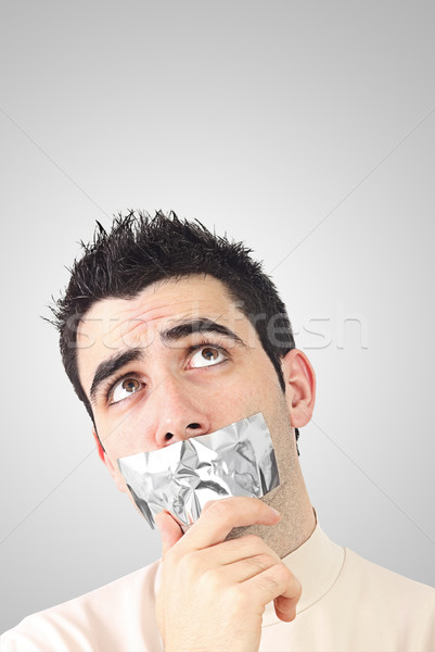 Curious young man having gray duct tape on his mouth Stock photo © jaycriss