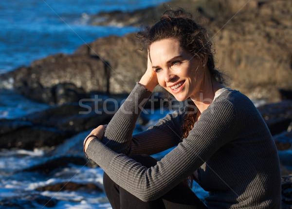 Szczęśliwy kobieta posiedzenia wybrzeża uśmiechnięta kobieta ocean Zdjęcia stock © jaykayl