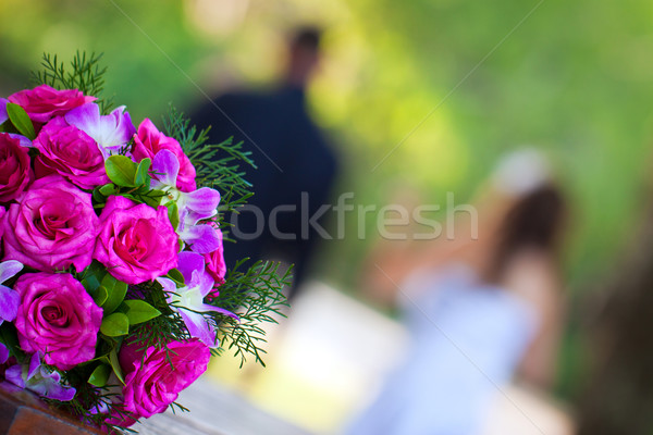 Newly wed couple walking away from a beautiful bridal bouquet Stock photo © jaykayl