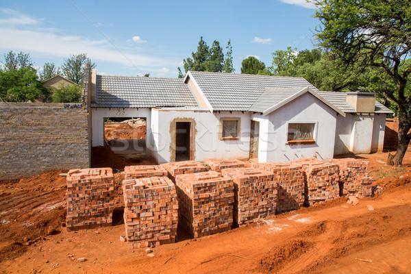 Téglák új ház egymásra pakolva hiányos ház biztonság Stock fotó © JFJacobsz