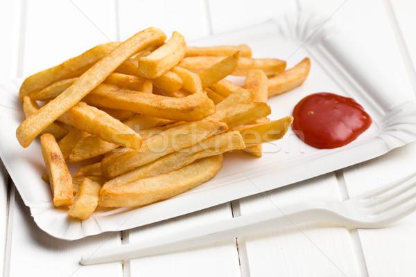 Patatine fritte ketchup carta piatto bianco tavolo in legno Foto d'archivio © jirkaejc