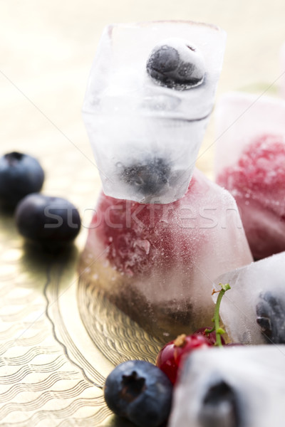 Fresh berry fruits frozen in ice cubes Stock photo © joannawnuk