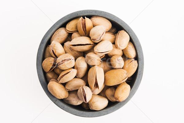 bowl of pistachios on white background Stock photo © joannawnuk