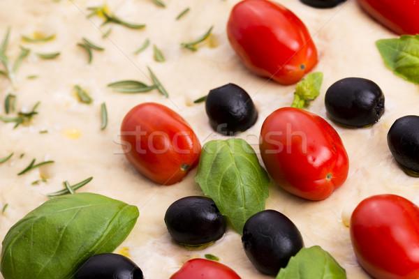 Focaccia with black olives, tomatoes and basil Stock photo © joannawnuk