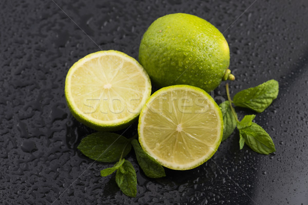 Green limes with mint and water drops on black background Stock photo © joannawnuk