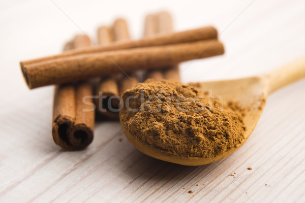 Cinnamon, whole sticks behind wooden spoon with a heap of powder Stock photo © joannawnuk