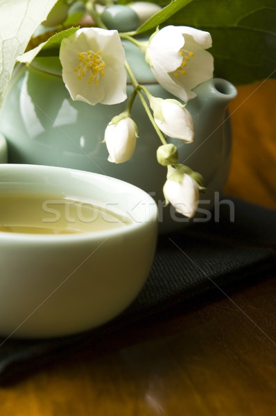 Green tea with jasmine in cup and teapot on wooden table Stock photo © joannawnuk