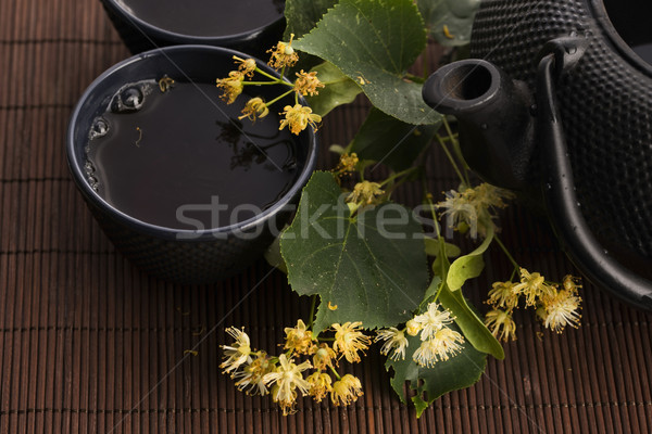 teapot and cup with linden tea and flowers Stock photo © joannawnuk