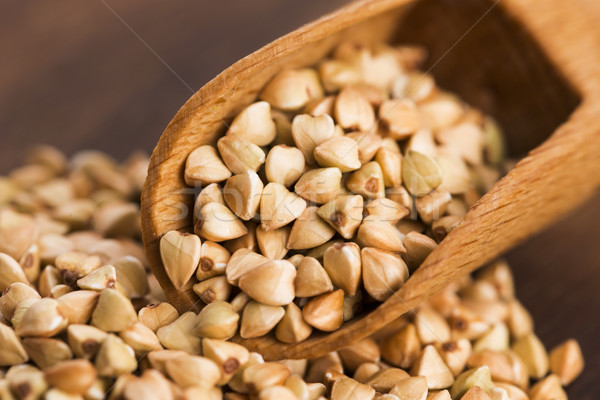 Buckwheat with a spoon on a wooden boards background Stock photo © joannawnuk