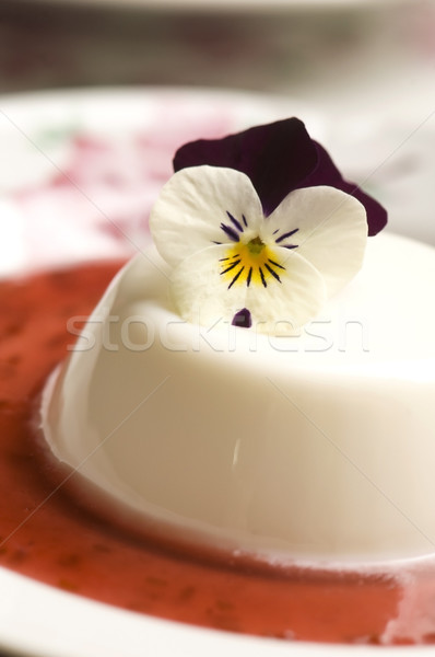 Vanilla panna cotta with berry sauce and spring flower Stock photo © joannawnuk