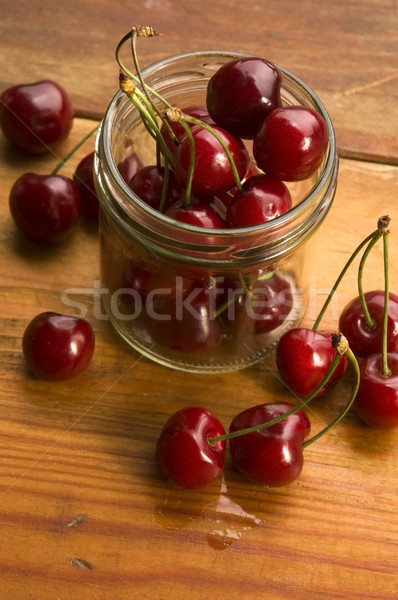 Cherry in glass jar isolated on the wooden background Stock photo © joannawnuk
