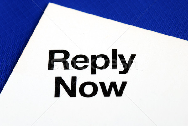 """Reply Now"" from a business reply postcard isolated on blue Stock photo © johnkwan"
