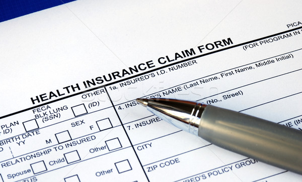 Stock photo: Filling the health insurance claim form isolated in blue