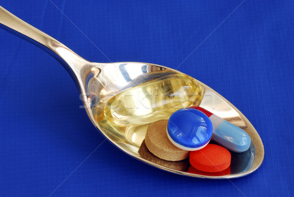 A spoonful of medicine including painkiller and vitamin isolated on blue Stock photo © johnkwan