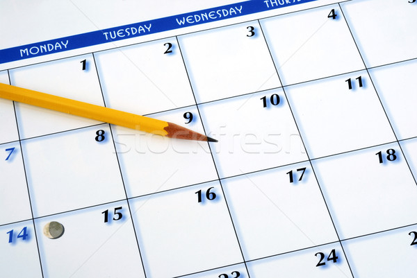 Planning the new month from a calendar with a pencil Stock photo © johnkwan