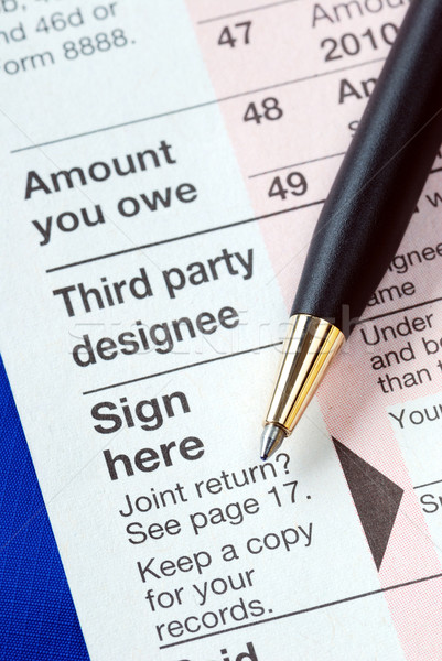 Sign the income tax return isolated on blue Stock photo © johnkwan