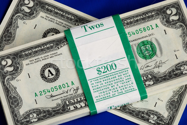 Piles of United States two dollar bills isolated on blue Stock photo © johnkwan
