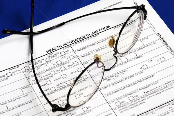 Fill the health insurance claim form isolated on blue Stock photo © johnkwan